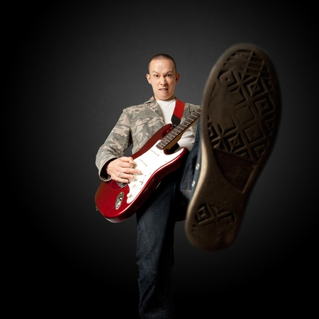 rocker with electric guitar putting foot in camera Stock Photo - 8891717