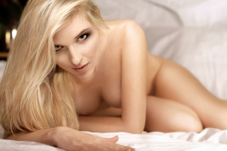nude in bed: beautiful woman in bed looking on camera, selective focus