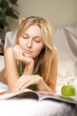 beautyful woman with green apple in bed photo