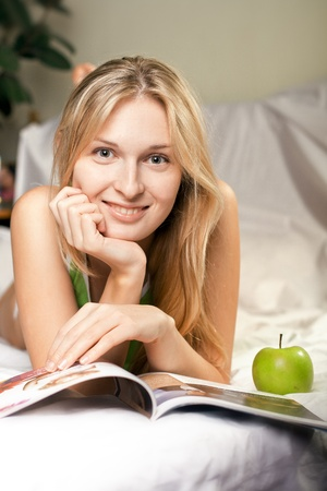 adult magazines: beautyful woman with green apple in bed Stock Photo