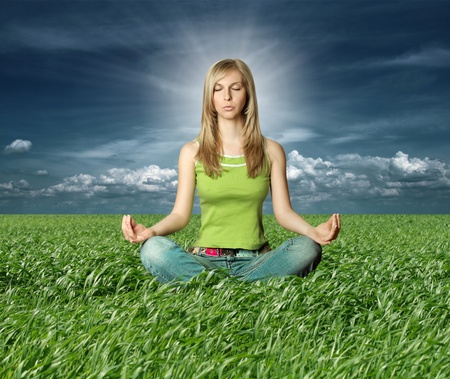 Blonde in yoga pose in green grass on blue summer sky photo