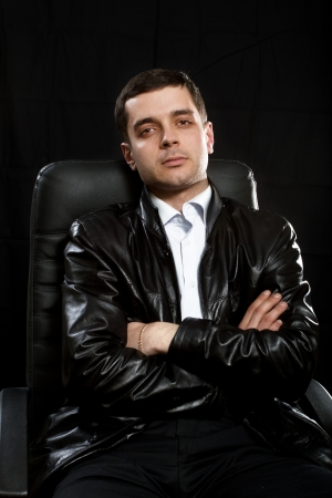 italian man: gangsrer male in leather jacket and leather chair