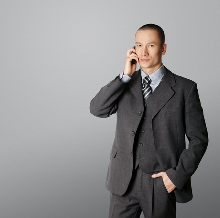 business man in suit speaking by the phone photo