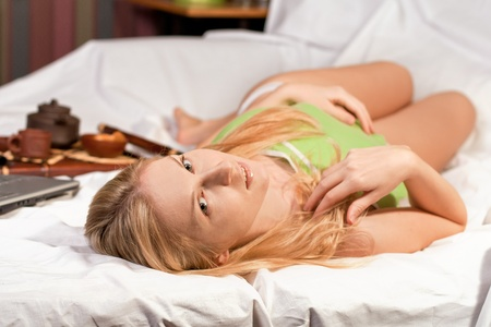 Beautiful blond female in bed with her laptop photo