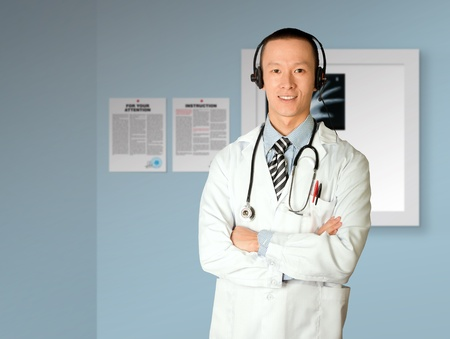 asian doctor with headphones, lab coat and stethoscope photo