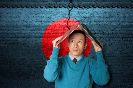 earthquakes: cracked brick wall as Japan flag and asian male with laptop Stock Photo