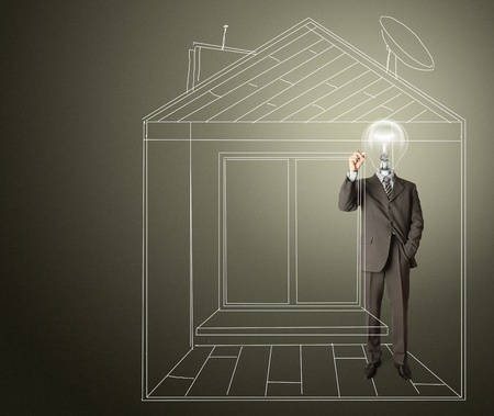 businessman with lamp-head and marker drawing house on glass writeboard photo