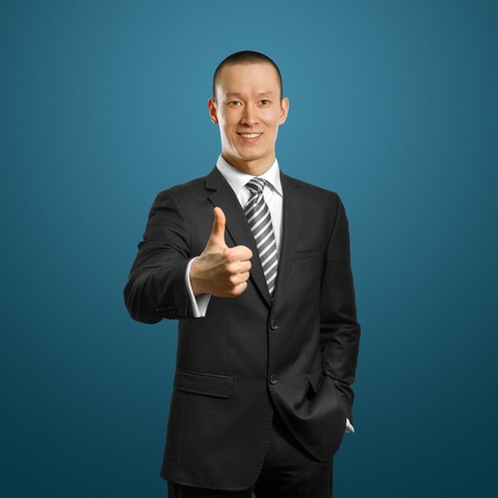 asian businessman in black suit shows well done against different backgrounds Stock Photo - 9336120
