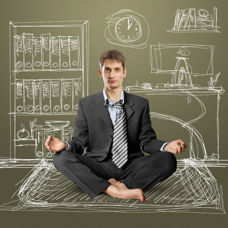 businessman in lotus pose meditating at the office photo