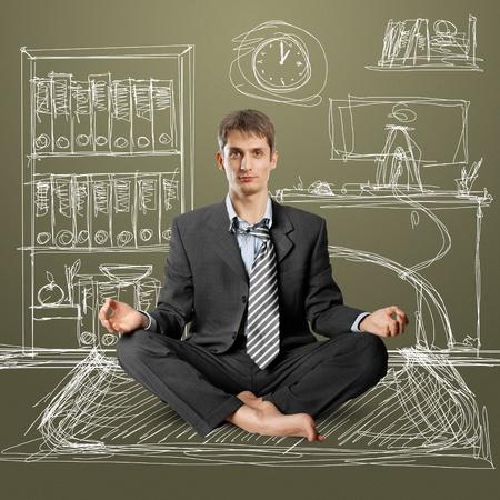 meditating: businessman in lotus pose meditating at the office Stock Photo