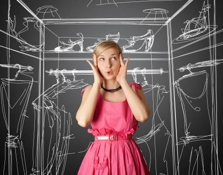 wardrobes: surprised girl in pink, looking up, with open hand Stock Photo