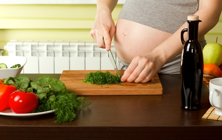 belly pepper: beautiful pregnant woman on kitchen with healthy food