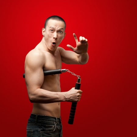 kung fu: funny muscular shaolin monk with nunchaku in his hands