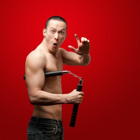moine: moine shaolin musculaire Funny avec nunchaku entre ses mains