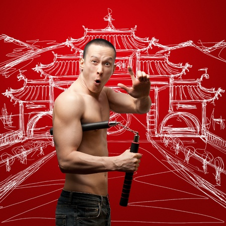 funny muscular shaolin monk with nunchaku in his hands photo