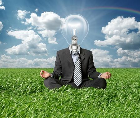 successful leadership: businessman in lotus pose and lamp-head in grass in green grass on blue summer sky Stock Photo