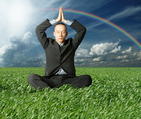 businessman in lotus pose in green grass on blue summer sky photo
