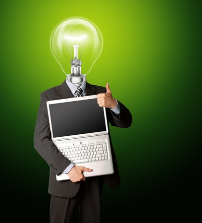 businessman with lamp-head with open laptop shows welldone photo