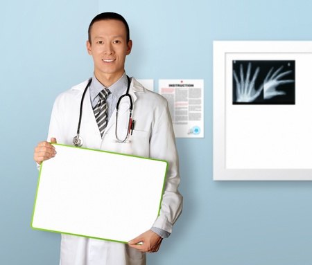 doctor with empty board in hith hands template, smiles at camera, isolated Фото со стока
