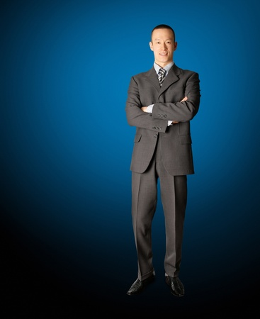graduation suit: smiling standing businessman in suit isolated on blue