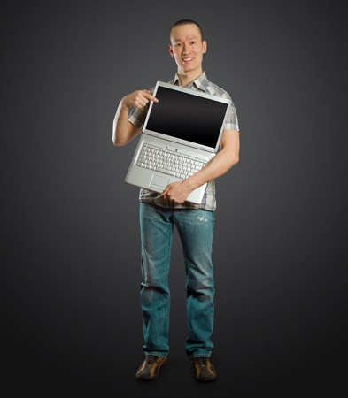 asian man with open laptop in his hands, smiles at camera photo