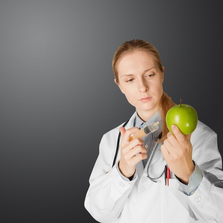 apple gmo: scientist woman does injection to an apple, isolated on different backgrounds