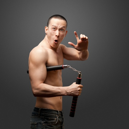 funny muscular shaolin monk with nunchaku in his hands Stock Photo - 10611324