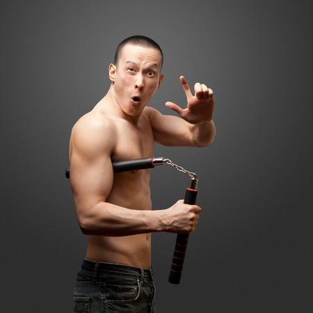 nunchaku: funny muscular shaolin monk with nunchaku in his hands