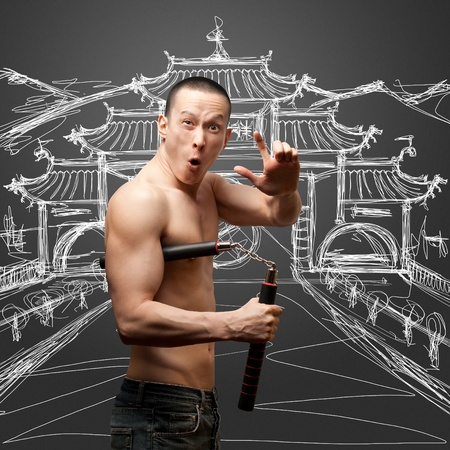 traditional weapon: funny muscular shaolin monk with nunchaku in his hands