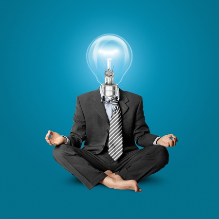 lamp-head businessman in lotus pose meditating at the office photo