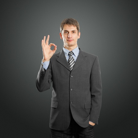 happy businessman shows OK against different backgrounds photo