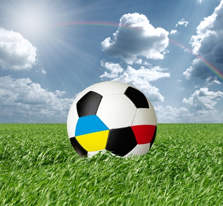 Soccer ball, Euro 2012 concept, ball with Ukraine and Poland flags, on green grass photo