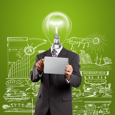 Idea concept, lamp head businessman in suit with touch pad in his hands Stock Photo - 12251579