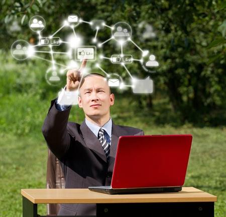 男性社会で赤のラップトップでネットワーク、屋外 pushs ボタン