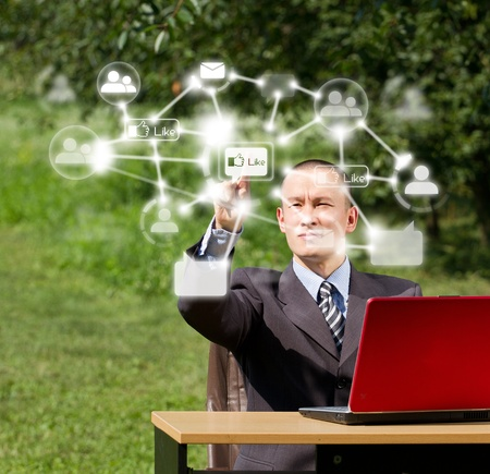 Man with red laptop in social networks outdoors, pushs the button Stock Photo - 12547519