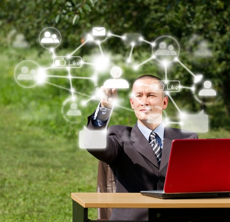 Man with red laptop in social networks outdoors, pushs the button Stock Photo