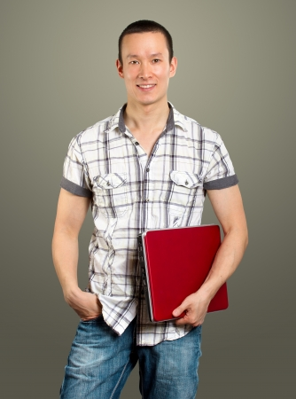 asian man with laptop in his hands, looking on camera photo