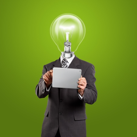 Idea concept, lamp head businessman in suit with touch pad in his hands photo