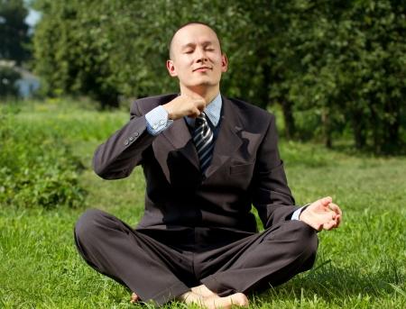 Man businessman meditating outdoors in lotus pose photo