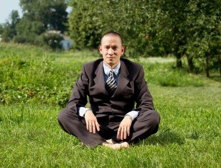 Tired Man businessman with stress meditating outdoors in lotus pose photo