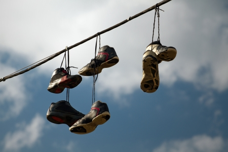 tennis shoe: Sneakers hanging on a telephone line, urban youth joke