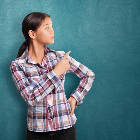 pointing finger: Asian girl with pointing finger showing something Stock Photo