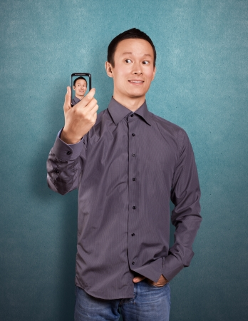 Asian man making an avatar on cell phone in social network photo