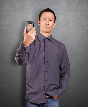 Asian man making an avatar on cell phone in social network Stock Photo - 16718514