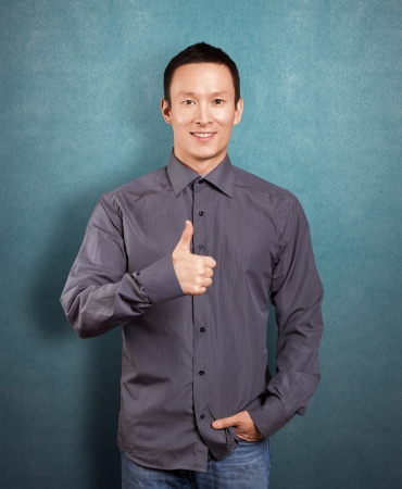 Asian business man shows well done against different backgrounds Stock Photo - 16718881
