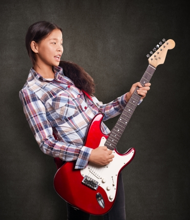 Asian girl playing the guitar and singing the song photo