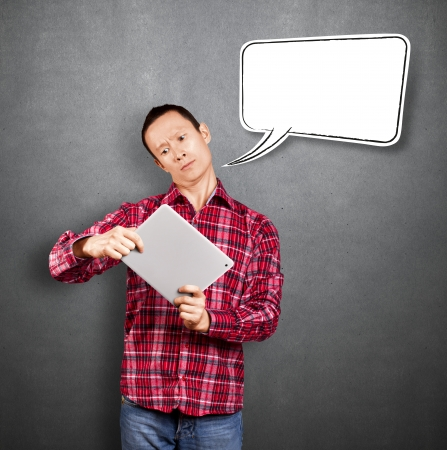 Asian man with speech bubble and touch pad in his hands embarrassed with news Stock Photo - 17237451
