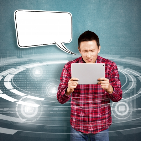 Asian man with speech bubble and touch pad in his hands embarrassed with news Stock Photo - 17237432