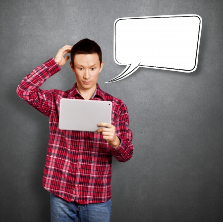 Asian man with speech bubble and touch pad in his hands embarrassed with news Stock Photo - 17237429