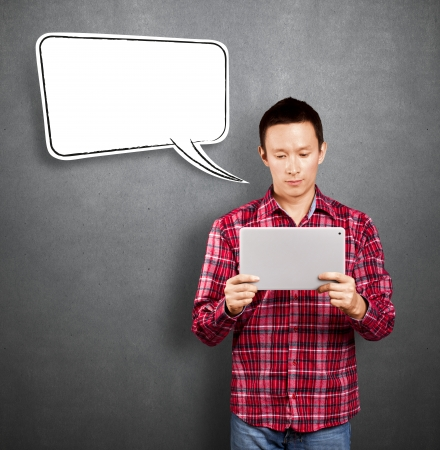 Asian man with speech bubble and touch pad in his hands embarrassed with news Stock Photo - 17237453